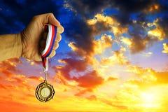 拿着一枚金黄奖牌的手 库存照片