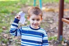 拿着一架纸飞机的逗人喜爱的男孩 免版税图库摄影