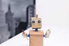 拿着一根导线和一支发光二极管在白色桌上的机器人 库存照片