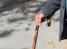 拿着一根木棍子的老人 免版税库存图片