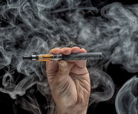 拿着一根电子香烟的手 免版税图库摄影