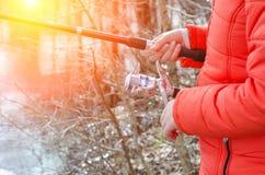 拿着一根钓鱼竿的女性手 免版税库存图片