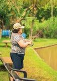 拿着一根钓鱼竿的老妇人,钩在湖的一条鱼 库存照片