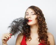 拿着一根黑羽毛的美丽的卷曲女孩 免版税库存图片