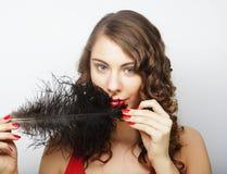 拿着一根黑羽毛的美丽的卷曲女孩 库存照片