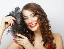 拿着一根黑羽毛的美丽的卷曲女孩 图库摄影