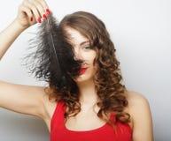 拿着一根黑羽毛的美丽的卷曲女孩 库存图片