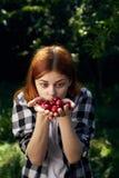 拿着一棵樱桃的妇女在庭院里 库存图片