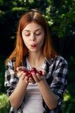 拿着一棵樱桃的美丽的少妇在庭院在夏天,花匠里 库存照片