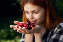 拿着一棵樱桃的年轻美丽的妇女在庭院在夏天,花匠里 免版税库存图片