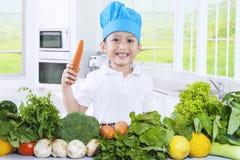 拿着一棵红萝卜的逗人喜爱的男孩在厨房里 库存照片