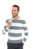 拿着一次性咖啡杯的冬天穿戴的愉快的年轻人 免版税库存照片
