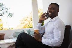 拿着一次性咖啡杯的商人,当谈话在咖啡馆时的电话 免版税库存照片