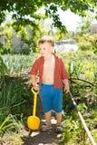 拿着一点塑料铁锹的男孩在一个晴天 库存图片