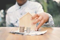 拿着一点木屋和硬币的手男孩 免版税库存图片