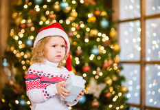 拿着一点礼物盒的哀伤的女婴 库存图片
