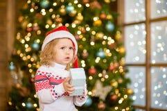 拿着一点礼物盒的哀伤的女婴 免版税库存照片