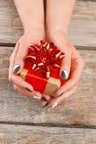 拿着一点礼物盒的被修剪的手 免版税库存照片