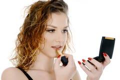 拿着一点镜子的雍妇女投入唇膏 免版税库存图片
