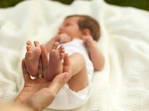 拿着一点baby& x27的手; s腿 免版税库存照片