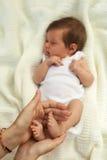 拿着一点baby& x27的手; s腿 库存照片