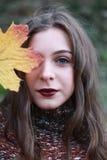 拿着一片金黄叶子的一个十几岁的女孩的画象对她的面孔 免版税库存图片