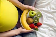 拿着一碗果子的怀孕的女孩 库存图片