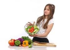 拿着一碗沙拉的一个年轻十几岁的女孩 免版税库存照片