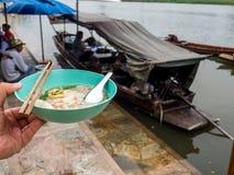 拿着一碗面条的左手 河后边,并且有面条小船 泰国生活方式 免版税库存照片