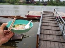 拿着一碗面条的左手 河后边,并且有面条小船 泰国生活方式 库存照片