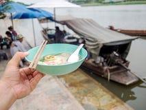 拿着一碗面条的左手 河后边,并且有面条小船 泰国生活方式 图库摄影