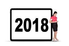 拿着一种数字式片剂的女实业家倾斜在广告牌的2018个数字 库存照片