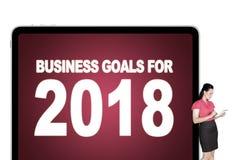 拿着一种数字式片剂的女实业家倾斜在2018年在广告牌的企业目标词 库存图片
