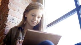 拿着一种数字式片剂的年轻人微笑的可爱的妇女坐在窗口附近 库存照片