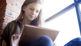 拿着一种数字式片剂的年轻人微笑的可爱的妇女坐在窗口附近 免版税库存照片