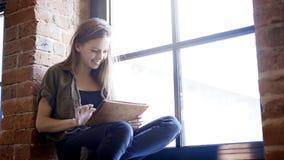 拿着一种数字式片剂的年轻人微笑的愉快的可爱的妇女坐窗口基石 库存图片