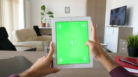 拿着一种数字式片剂的男性手个人计算机与绿色屏幕色度大模型 影视素材