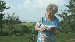 拿着一种数字式片剂的老妇人80s户外 股票录像