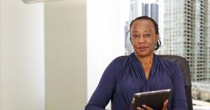 拿着一种片剂的一名非裔美国人的女实业家在她的芝加哥办公室 免版税库存图片