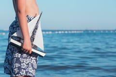 拿着一艘帆船的男孩在海边特写镜头 库存照片