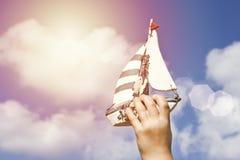 拿着一艘手工制造船的孩子的手 库存照片