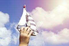 拿着一艘手工制造船的孩子的手 免版税库存图片