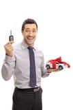 拿着一辆关键和一辆模型汽车的快乐的商人 库存照片