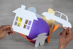 拿着一辆汽车和一个房子纸的人的综合图象 库存照片
