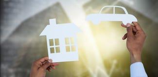 拿着一辆汽车和一个房子纸的人的综合图象 免版税库存图片