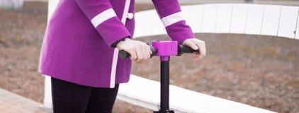 拿着一辆电滑行车的方向盘的年轻女人的手 可看见的桃红色-紫色外套 没有面孔 ?? 免版税图库摄影
