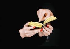 拿着一部被打开的圣经的两只妇女的手 库存图片