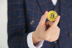拿着一金黄bitcoin -国际真正cryptocurrency的标志的衣服的人 在白色 免版税库存照片
