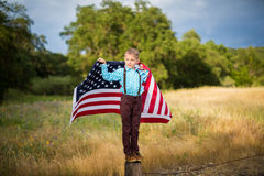 拿着一面大美国国旗的一个年轻男孩显示他自己的国家的爱国心,团结状态 免版税库存图片