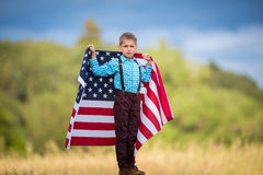 拿着一面大美国国旗的一个年轻男孩显示他自己的国家的爱国心,团结状态 库存图片